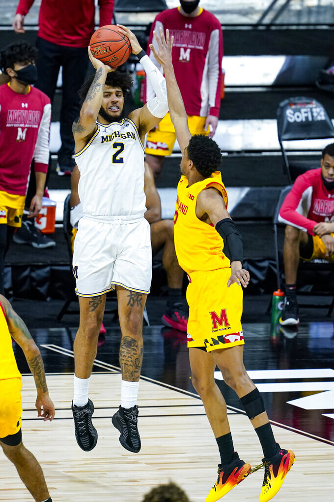 Michigan forward Isaiah Livers (2) shoots over Maryland guard Aaron Wiggins (2) in the first half of an NCAA college basketball game at the Big Ten Conference tournament in Indianapolis, Friday, March 12, 2021. (AP Photo/Michael Conroy)