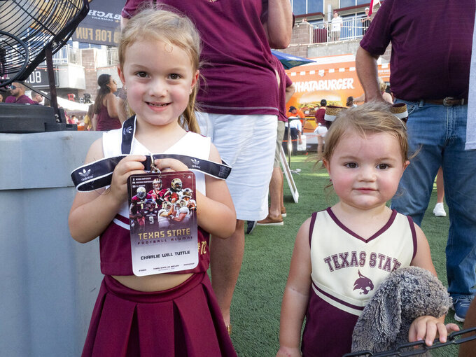 Former Texas State football player Charlie Will Tuttle's daughters Logan, 4, left, and Jodi, 2, right, wear their uniforms to the team's NCAA college football game against Baylor, Saturday, Sept. 4, 2021, in San Marcos, Texas. (AP Photo/Michael Thomas)