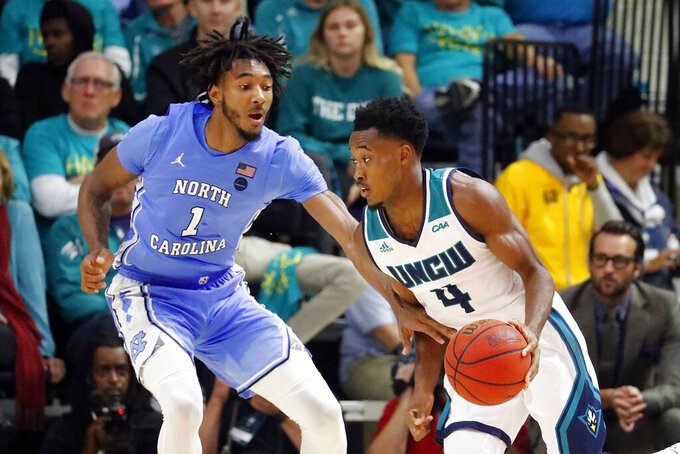 Leaky Black (1) guards against North Carolina Wilmington's Mike Okauru (4) during the second half of an NCAA college basketball game in Wilmington, N.C., Friday, Nov. 8, 2019. (AP Photo/Karl B DeBlaker)