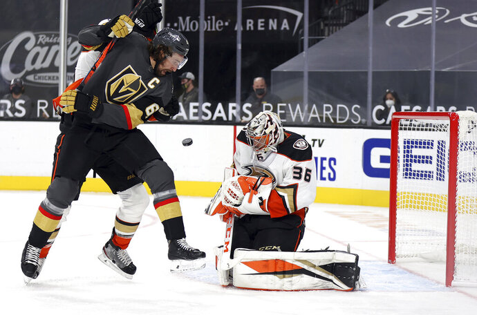 Anaheim Ducks goalie John Gibson (36) blocks a shot as Vegas Golden Knights right wing Mark Stone (61) looks for the rebound during the second period of an NHL hockey game Thursday, Jan. 14, 2021, in Las Vegas. (AP Photo/Isaac Brekken)