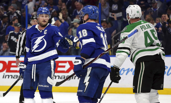 Tampa Bay Lightning's Steven Stamkos, left, celebrates his goal with Ondrej Palat, of the Czech Republic, as Dallas Stars' Roman Polak, of the Czech Republic, skates past during the second period of an NHL hockey game Thursday, Feb. 14, 2019, in Tampa, Fla. (AP Photo/Mike Carlson)