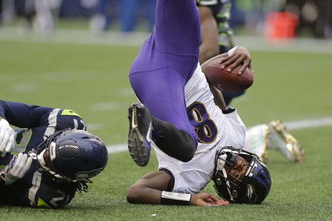 Baltimore Ravens quarterback Lamar Jackson (8) comes down next to Seattle Seahawks cornerback Tre Flowers, left, as he scores a touchdown on a fourth-down keeper play during the second half of an NFL football game, Sunday, Oct. 20, 2019, in Seattle. (AP Photo/John Froschauer)