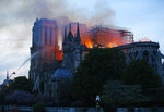 A firefighter tackles the blaze as flames and smoke rise from Notre Dame cathedral as it burns in Paris, Monday, April 15, 2019. Massive plumes of yellow brown smoke is filling the air above Notre Dame Cathedral and ash is falling on tourists and others around the island that marks the center of Paris. (AP Photo/Michel Euler)