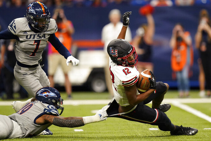 Lamar wide receiver Marcellus Johnson (12) is pulled down behind the line of scrimmage by UTSA defensive lineman Trumane Bell II (49) during the first half of an NCAA college football game Saturday, Sept. 11, 2021, in San Antonio. (AP Photo/Eric Gay)