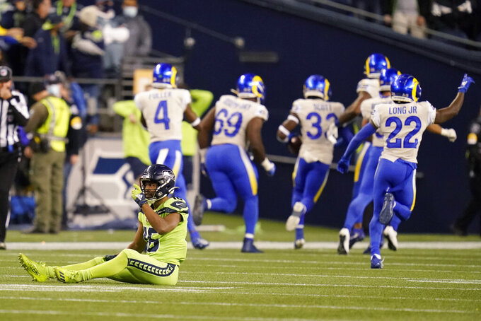 Seattle Seahawks wide receiver Tyler Lockett, left, sits on the turf after he got tripped up and had a pass intended for him intercepted by Los Angeles Rams safety Nick Scott (33) during the second half of an NFL football game, Thursday, Oct. 7, 2021, in Seattle. The Rams won 26-17. (AP Photo/Elaine Thompson)