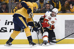 Nashville Predators defenseman Dan Hamhuis (5) and Calgary Flames left wing Matthew Tkachuk (19) compete for the puck during the first period of an NHL hockey game Thursday, Oct. 31, 2019, in Nashville, Tenn. (AP Photo/Mark Zaleski)