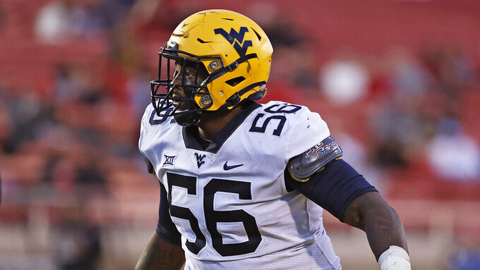 West Virginia defensive tackle Darius Stills (56) is shown during an NCAA college football game against Texas Tech, Saturday, Oct. 24, 2020, in Lubbock, Texas. Stills was selected to The Associated Press All-America first-team defense, Monday, Dec. 28, 2020. (AP Photo/Brad Tollefson)