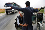 In this March 28, 2018 photo, a Kurdish policeman checks an Arab Syrian man at a checkpoint controlled by The U.S.-backed Syrian Democratic Forces, SDF, on a highway in Hassakeh province, Syria. SDF defeated IS in March but the Kurdish-led force is now facing protests by local Arab tribesmen in Deir el-Zour province. If the protests turn to an all-out uprising against the SDF it could be a blow to Washington as President Trump has plans to reduce America's military presence in Syria. (AP Photo/Hussein Malla)