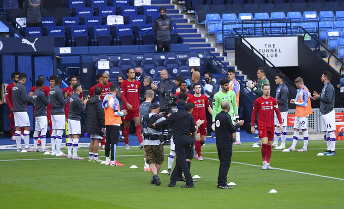 Liverpool players walk through a guard of honor from the Manchester City team ahead of their English Premier League soccer match between Manchester City and Liverpool at Etihad Stadium in Manchester, England, Thursday, July 2, 2020. (AP Photo/Laurence Griffiths,Pool)