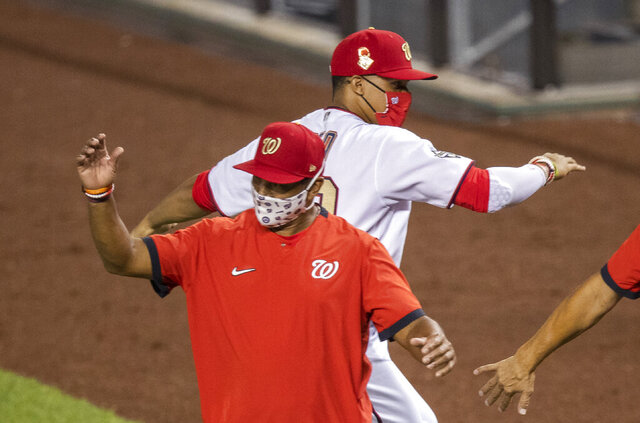Washington Nationals' Juan Soto back, celebrates with manager Dave Martinez, after the Nationals defeated the New York Mets 5-3 a baseball game in Washington, Tuesday, Aug. 4, 2020. (AP Photo/Manuel Balce Ceneta)