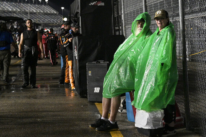 Fans cover up on pit road during a rain delay in the NASCAR Xfinity Series auto race at Daytona International Speedway, Friday, Aug. 27, 2021, in Daytona Beach, Fla. (AP Photo/Phelan M. Ebenhack)