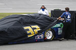 Crews cover the car of driver Corey LaJoie as inclement weather rolls in prior to a NASCAR Cup Series auto race at Talladega Superspeedway in Talladega Ala., Sunday, June 21, 2020. (AP Photo/John Bazemore)