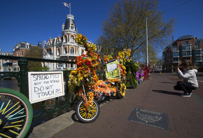 A woman takes images of decorated bicycles, or flower bikes, as sign warns for the risk of spreading the coronavirus in Amsterdam, Netherlands, Sunday, April 19, 2020. (AP Photo/Peter Dejong)