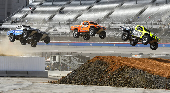 Blade Hildebrand, right, leads the field over a jump during the Outdoor Powersports Offroad Rumble SST Race prior to a NASCAR Cup auto race at Texas Motor Speedway, Sunday, March 31, 2019, in Fort Worth, Texas. (AP Photo/Larry Papke)