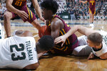 Minnesota's Marcus Carr, center, and Michigan State's Xavier Tillman (23) and Thomas Kithier, right, vie for a loose ball during the first half of an NCAA college basketball game Thursday, Jan. 9, 2020, in East Lansing, Mich. (AP Photo/Al Goldis)