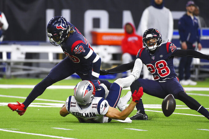 Houston Texans strong safety Justin Reid (20) and cornerback Vernon III Hargreaves (28) break up a pass intended for New England Patriots wide receiver Julian Edelman (11) during the first half of an NFL football game Sunday, Dec. 1, 2019, in Houston. (AP Photo/Eric Christian Smith)