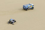 Truck driver Eduard Nikolaev, of Russia, and co-driver Evgeny Yakovlev, of Russia, race their Kamaz pass the stuck Can-Am of driver Leo Larrauri and co-driver Fernando Imperatrice, both of Argentina, race their Can-Am during the first stage of the 2018 Dakar Rally between Lima and Pisco, Peru, Saturday, Jan. 6, 2018. (AP Photo/Ricardo Mazalan)
