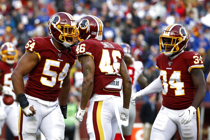 Washington Redskins linebacker Nate Orchard, left, celebrates his blocked punt with teammates Maurice Smith (46) and Wendell Smallwood (34) during the second half of an NFL football game against the New York Giants, Sunday, Dec. 22, 2019, in Landover, Md. (AP Photo/Patrick Semansky)