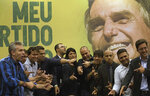 Backdropped by a picture of the presidential candidate Jair Bolsonaro of the right wing Social Liberal Party, recently elected Rio de Janeiro state congressmen, pose for a picture point their fingers like a gun mimicking Bolsonaro, after a press conference in Rio de Janeiro, Brazil, Thursday, Oct. 11, 2018. Bolsonaro will face Workers Party presidential candidate Fernando Haddad in a presidential runoff on Oct. 28. (AP Photo/Leo Correa)