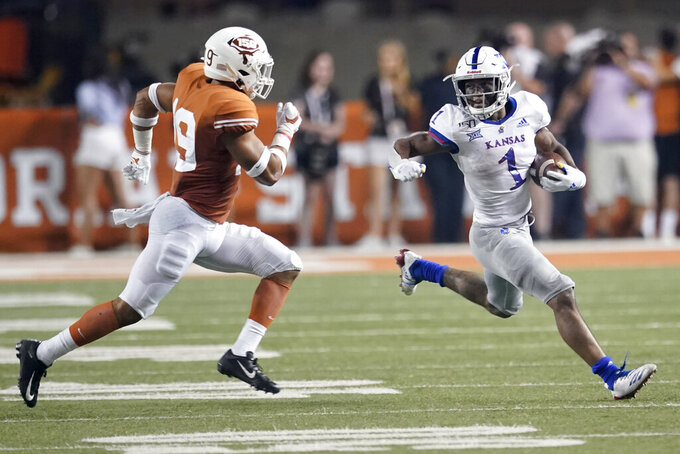 FILE - In this Oct. 19, 2019, file photo, Kansas' Pooka Williams Jr. (1) runs for a long gain as Texas' Brandon Jones (19) pursues during the second half of an NCAA college football game in Austin, Texas. Williams' first two seasons with the Jayhawks have produced 2,186 yards rushing at 6.0 yards per carry and 10 touchdowns. (AP Photo/Chuck Burton, File)
