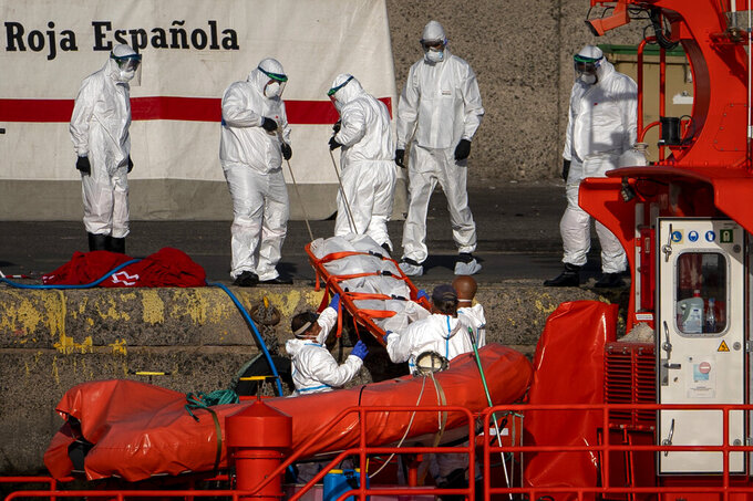 FILE, in this on Friday, Aug. 21, 2020 file photo, emergency workers carry a migrant's body after being found dead by the Spanish Maritime Rescue Service, at the Arguineguin port in Gran Canaria island, Spain. The number of migrants and asylum seekers that have reached Europe in 2020 is the lowest it has been in the past decade. But deaths and disappearances on sea routes to the continent remain alarmingly high with only a small fraction of victims being identified and bodies recovered according to a report released Friday by the United Nations migration agency. (AP Photo/Emilio Morenatti, file)