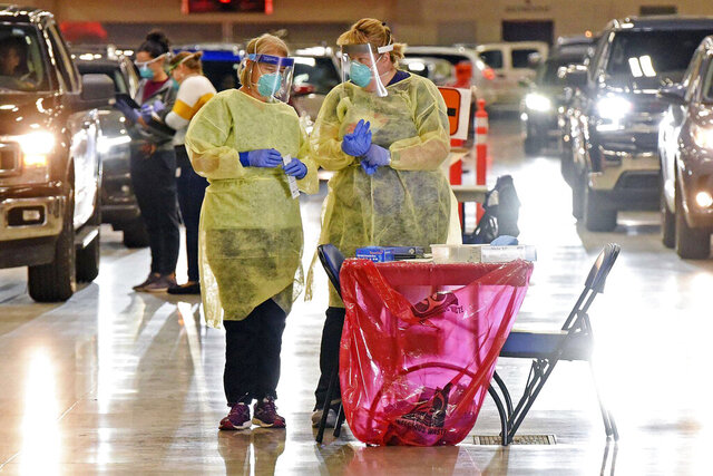 FILE - In this Sept. 8, 2020, file photo, Bismarck-Burleigh Public Health nurses Crys Kuntz, left, and Sara Nelson confer inside the Bismarck Event Center in Bismarck, N.D., where vehicles were lined up for the weekly drive-thru COVID-19 testing. The coronavirus tightened its grip on the American heartland, with hospitals in Wisconsin and North Dakota running low on space, and the NFL postponing a game over an outbreak that's hit the Tennessee Titans football team. (Tom Stromme/The Bismarck Tribune via AP, File)