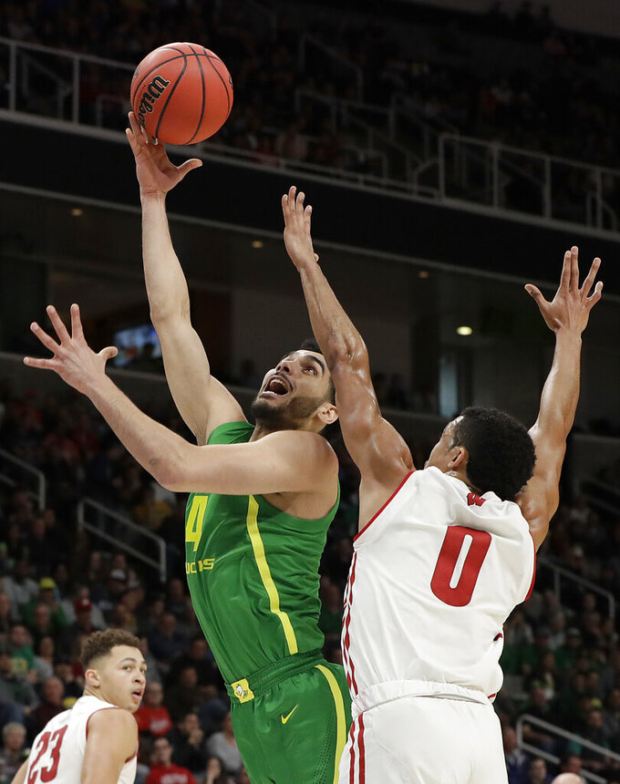 Oregon guard Ehab Amin (4) shoots against Wisconsin guard D'Mitrik Trice (0) during the first half of a first-round game in the NCAA men's college basketball tournament Friday, March 22, 2019, in San Jose, Calif. (AP Photo/Chris Carlson)