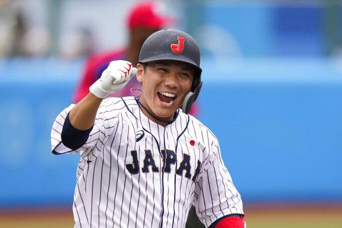 Japan's Hayato Sakamoto celebrates his walk-off single in the ninth inning of a baseball game against the Dominican Republic at the 2020 Summer Olympics, Wednesday, July 28, 2021, in Fukushima, Japan. Japan won 4-3. (AP Photo/Jae C. Hong)