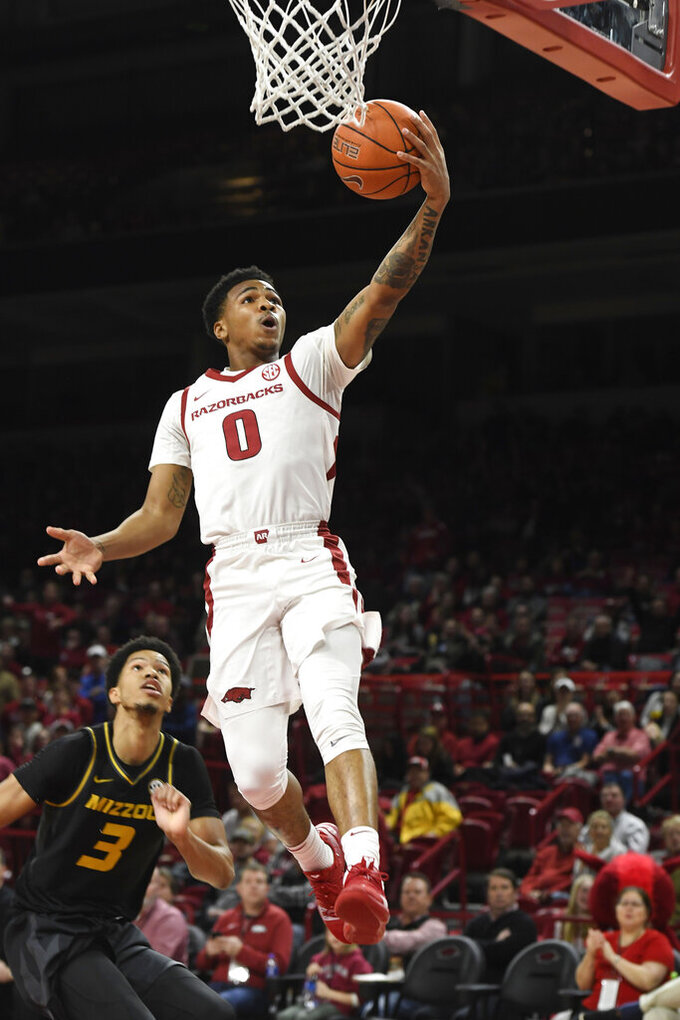 Arkansas guard Desi Sills (0) lays the ball up in front of Missouri's Ronnie Suggs (3) during the first half of an NCAA college basketball game, Wednesday, Jan. 23, 2019, in Fayetteville, Ark. (AP Photo/Michael Woods)