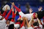 Members of team Japan celebrate after a softball game against the United States at the 2020 Summer Olympics, Tuesday, July 27, 2021, in Yokohama, Japan. Japan won 2-0. (AP Photo/Sue Ogrocki)