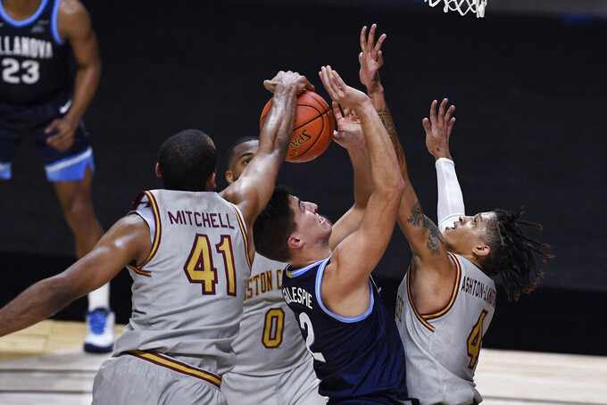 Boston College's Steffon Mitchell, left, stops a shot attempt by Villanova's Collin Gillespie as Boston College's Frederick Scott, back, and Makai Ashton-Langford right, defend during the first half of an NCAA college basketball game Wednesday, Nov. 25, 2020, in Uncasville, Conn. (AP Photo/Jessica Hill)