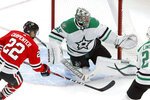 Dallas Stars goaltender Anton Khudobin (35) makes a glove save as Chicago Blackhawks' Ryan Carpenter looks for a rebound during the second period of an NHL hockey game Tuesday, Nov. 26, 2019, in Chicago. (AP Photo/Charles Rex Arbogast)