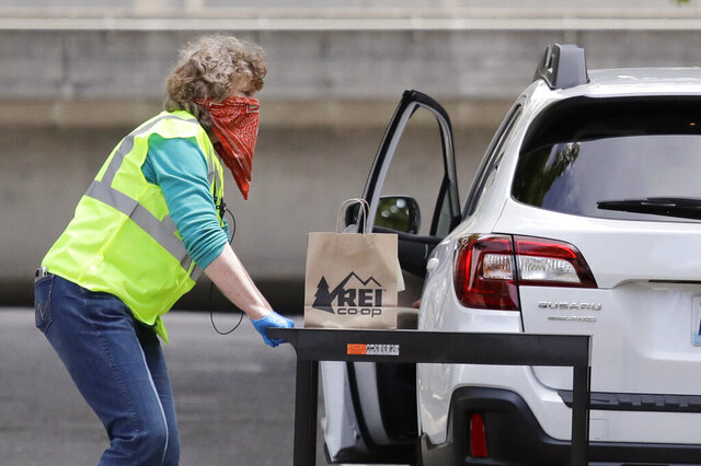 REI Co-op worker Sherry Johnson moves a cart into position for a customer to pick up an online order curbside outside the flagship store Wednesday, May 13, 2020, in Seattle. REI began offering the pick-up option to customers Wednesday morning under the state's new coronavirus rules, following a closure of the stores during the outbreak. The Seattle-area openings follow last week's announcement by Gov. Jay Inslee that nonessential retailers can reopen for curbside pickup in the first of the state's four-phase reopening plan. (AP Photo/Elaine Thompson)
