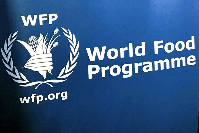 FILE - In this Nov. 6, 2017 file photo, the U.N. World Food Program's logo is seen at the agency's headquarters in New York. The United Nations says the ranks of the world's hungry grew by 10 million last year and warns that the coronavirus pandemic could push as many as 130 million more people into chronic hunger this year. The grim assessment is contained in an annual report released Monday, July 13 2020 by the five U.N. agencies that produced it.  (AP Photo/Robert Bumstead, File)