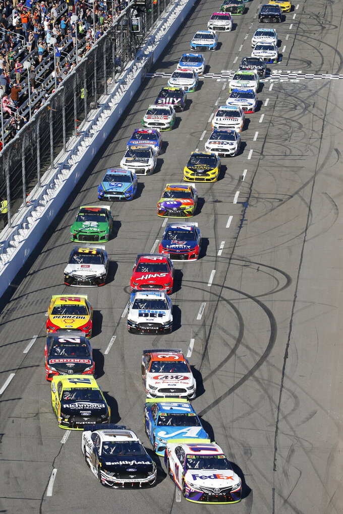 Denny Hamlin (11) leads the field at the start of a NASCAR Cup Series race at Martinsville Speedway in Martinsville, Va., Sunday, Oct. 27, 2019. (AP Photo/Steve Helber)