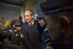 Former Guatemalan President Alvaro Colom is escorted by police to a courtroom in Guatemala City, Tuesday, Feb. 13, 2018. Colom, who governed from 2008 to 2012, has been detained in a corruption case according to special prosecutor Juan Francisco Sandoval. (AP Photo/Luis Soto)