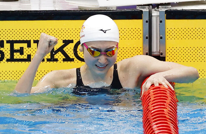 Japanese swimmer Rikako Ikee celebrates after winning the women's 100-meter butterfly at the Japan's national championships at Tokyo Aquatics Centre in Tokyo, Sunday, April 4, 2021.  Ikee on Sunday qualified for the Tokyo Olympics just two years after the was diagnosed with leukemia. (Kyodo News via AP)