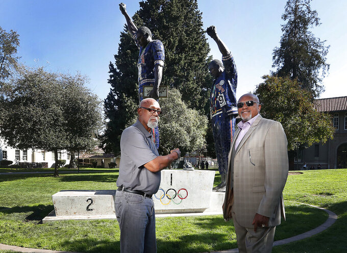 FILE - In this Oct. 17, 2018, file photo, John Carlos, left, and Tommie Smith pose for a photo in front of statue that honors their iconic, black-gloved protest at the 1968 Olympic Games, on the campus of San Jose State University in San Jose, Calif. The U.S. Olympic and Paralympic Committee heeded calls from American athletes, announcing Thursday, Dec. 10, 2020, that it won't sanction them for raising their fists or kneeling on the medals stand at next year's Tokyo Games and beyond. (AP Photo/Tony Avelar, File)