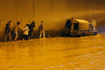 People walk through a flooded tunnel in Beirut's southern suburb of Ouzai, Lebanon, Monday, Dec. 9, 2019. A rainstorm paralyzed parts of Lebanon's capital Beirut on Monday, turning streets to small rivers, stranding motorists inside their vehicles and damaging homes in some areas.  (AP Photo/Bilal Hussein)