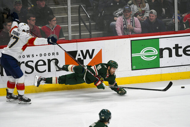 Florida Panthers left wing Frank Vatrano, left, gets a two minute penalty as he trips Minnesota Wild winger Jason Zucker during the third period of an NHL hockey game Monday, Jan. 20, 2020, in St. Paul, Minn. The Panthers won 5-4. (AP Photo/Craig Lassig)