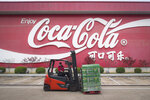 In this Tuesday, March 24, 2020, photo released by China's Xinhua News Agency, a worker wearing a face mask drives a forklift at a Swire Coca-Cola Beverages Hubei Limited plant in Wuhan in central China's Hubei Province. According to Chinese state media, the plant restarted some production lines on Monday. While many migrant workers across China remain trapped by travel bans due to the coronavirus, some industrial production has returned to action, including in the crucial auto manufacturing industry, which is largely based in Wuhan, and in businesses that provide critical links in global supply chains. The new coronavirus causes mild or moderate symptoms for most people, but for some, especially older adults and people with existing health problems, it can cause more severe illness or death. (Xiao Yijiu/Xinhua via AP)