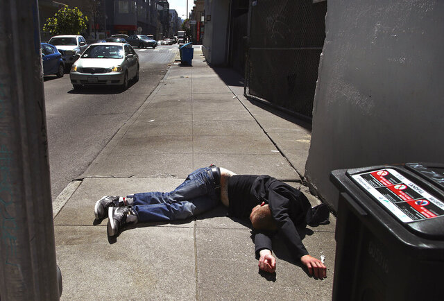 FILE - In this April 26, 2018, file photo, a man lies on the sidewalk beside a recyclable trash bin in San Francisco. A record 621 people died of drug overdoses in San Francisco so far this year, a staggering number that far outpaces the 173 deaths from COVID-19 the city has seen thus far. The crisis fueled by the powerful painkiller fentanyl could have been far worse if it wasn't for the nearly 3,000 times Narcan was used from January to the beginning of November to save someone from the brink of death, the San Francisco Chronicle reported Saturday, Dec. 19, 2020. (AP Photo/Ben Margot, File)