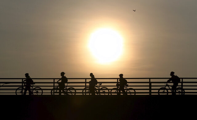 Commuters walk their bicycles across a pedestrian bridge, in Bogota, Colombia, Tuesday, March 17, 2020. Officials in Colombia's capital have expanded bike routes, encouraging people to abandon crowded public transportation and the risk of catching the coronavirus. The vast majority of people recover from the new virus. (AP Photo/Fernando Vergara)