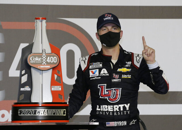 William Byron stands with his trophy in Victory Lane after winning the NASCAR Cup Series auto race at Daytona International Speedway, Saturday, Aug. 29, 2020, in Daytona Beach, Fla. (AP Photo/Terry Renna)