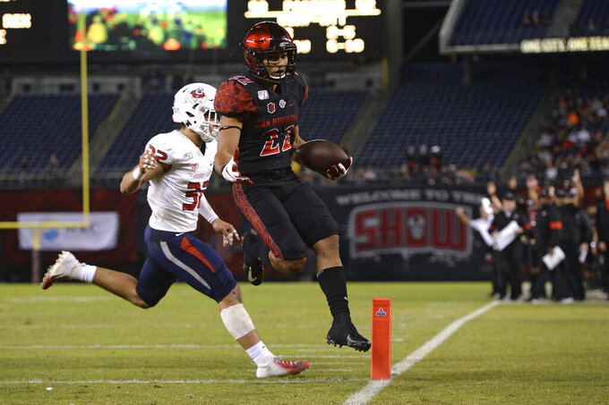 San Diego State running back Chase Jasmin (22) scores a touchdown ahead of Fresno State defensive back Evan Williams during the first half of the NCAA college football game Friday, Nov. 15, 2019, in San Diego. (AP Photo/Orlando Ramirez)
