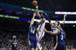 Philadelphia 76ers' Joel Embiid, center, goes up to shoot against New Orleans Pelicans' Kenrich Williams (34), Jaxson Hayes (10), Josh Hart (3) and Jrue Holiday (11) during the second half of an NBA basketball game, Friday, Dec. 13, 2019, in Philadelphia. (AP Photo/Matt Slocum)