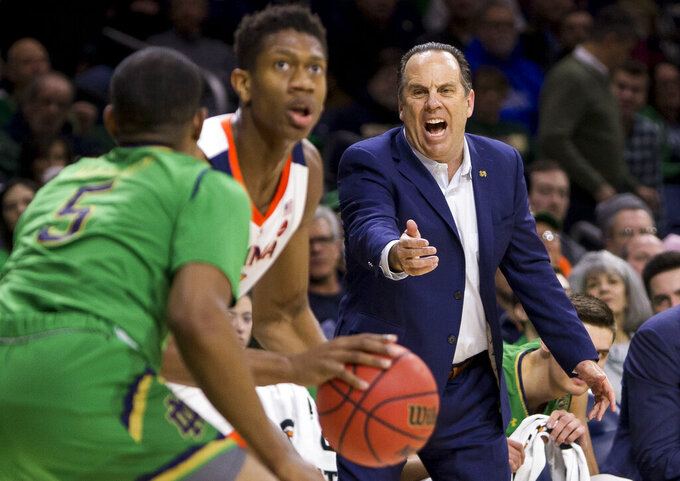 Notre Dame head coach Mike Brey yells to his players as Notre Dame's D.J. Harvey (5) defends against Virginia's De'Andre Hunter during the first half of an NCAA college basketball game Saturday, Jan. 26, 2019, in South Bend, Ind. (AP Photo/Robert Franklin)