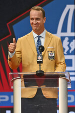 Peyton Manning, a member of the Pro Football Hall of Fame Class of 2021, gives a thumbs-up as he speaks during the induction ceremony at the Pro Football Hall of Fame, Sunday, Aug. 8, 2021, in Canton, Ohio. (AP Photo/David Richard)