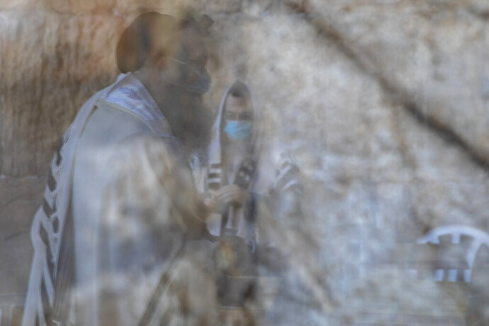 Ultra-Orthodox Jewish men wearing face masks, are reflected on a door window, as they pray ahead of Yom Kippur, the holiest day in the Jewish year which starts at sundown Sunday during a three-week nationwide lockdown to curb the spread of the coronavirus at the Western Wall, the holiest site where Jews can pray in Jerusalem's old city, Sunday, Sept. 27, 2020. (AP Photo/Ariel Schalit)