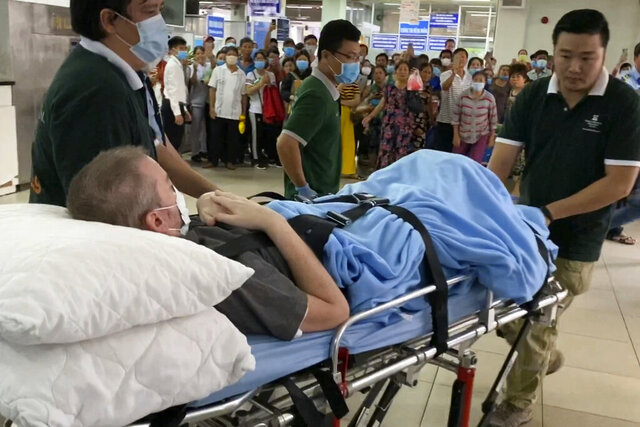 ADDS NAME OF THE PILOT AND UPDATES CAPTION - A British pilot, identified by the official Vietnam News Agency as Stephen Cameron, is carried on a stretcher in Ho Chi Minh city, Vietnam Saturday, July 11, 2020. The pilot who was Vietnam's most critical COVID-19 patient has been discharged from a hospital, less than a week after doctors said he was virus-free and healthy enough to return home to Scotland. Vietnam has gone all out to save the 42-year-old man. (AP Photo/Hieu Dinh)